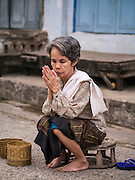 "11 MARCH 2013 - LUANG PRABANG, LAOS:  A woman prays after the tak bat in Luang Prabang. The ""Tak Bat"" is a daily ritual in most of Laos (and other Theravada Buddhist countries like Thailand and Cambodia). Monks leave their temples at dawn and walk silently through the streets and people put rice and other foodstuffs into their alms bowls. Luang Prabang, in northern Laos, is particularly well known for the morning ""tak bat"" because of the large number temples and monks in the city. Most mornings hundreds of monks go out to collect alms from people.   PHOTO BY JACK KURTZ"