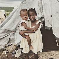 A young Haitian-descent girl holds her baby sister outside of the tent the live in