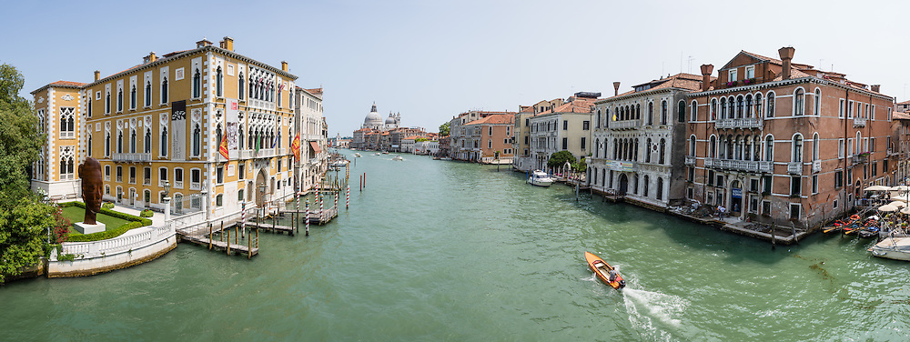 "See Basilica di Santa Maria della Salute from Ponte dell'Accademia bridge on the Grand Canal in Venice, Italy. The bridge links the sestiere of San Marco and Dorsoduro and is named for the Accademia di Belle Arti di Venezia. The original 1854 steel bridge was replaced by a wooden one in 1933 and 1985. Lovers like to attach padlocks (""love locks"") to the metal hand rails of the bridge (but are discouraged from doing so by Venice authorities). The yellow and white building at left is Istituto Veneto di Scienze Lettere ed Arti / Palazzo Cavalli Franchetti. Venice (Venezia) is the capital of Italy's Veneto region, named for the ancient Veneti people from the 900s BC. The romantic ""City of Canals"" stretches across 100+ small islands in the marshy Venetian Lagoon along the Adriatic Sea in northeast Italy, between the mouths of the Po and Piave Rivers. The Republic of Venice was a major maritime power during the Middle Ages and Renaissance, a staging area for the Crusades, and a major center of art and commerce (silk, grain and spice trade) from the 1200s to 1600s. The wealthy legacy of Venice stands today in a rich architecture combining Gothic, Byzantine, and Arab styles. This panorama was stitched from 10 overlapping photos."