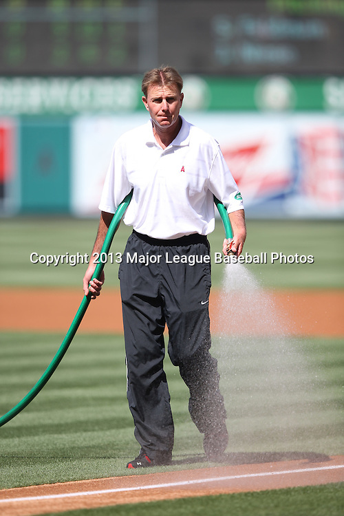 ANAHEIM, CA - JUNE 15:  A groundskeeper waters the infield before the Los Angeles Angels of Anaheim game against the New York Yankees on Saturday, June 15, 2013 at Angel Stadium in Anaheim, California. The Angels won the game 6-2. (Photo by Paul Spinelli/MLB Photos via Getty Images)