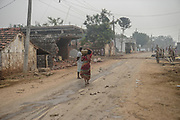 A woman carries a pot of water through a street in village Gorikothapally, Telangana, Indiia, on Friday, February 8, 2019. Photographer: Suzanne Lee for Safe Water Network