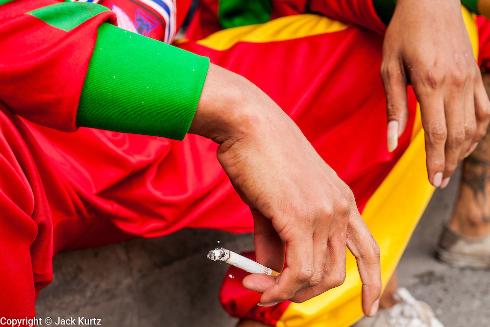 14 OCTOBER 2012 - BANGKOK, THAILAND:  A man holds a cigarette while smoking on a street in Bangkok, Thailand. Thailand and the Philippines are involved in a dispute over cigarette taxes. Philippine trade officials allege that Thailand charges an unfair import tax on Philippine cigarettes. Thai officials have responded that they have taken the matter under advisement. Philippine officials said they may take the issue to the World Trade Organization if Thailand doesn't respond by Oct. 15.   PHOTO BY JACK KURTZ