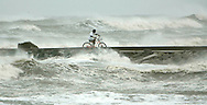 Benny Salas rides his bike on a pier in Galveston, Texas as Hurricane Rita approached September 23, 2005. ..