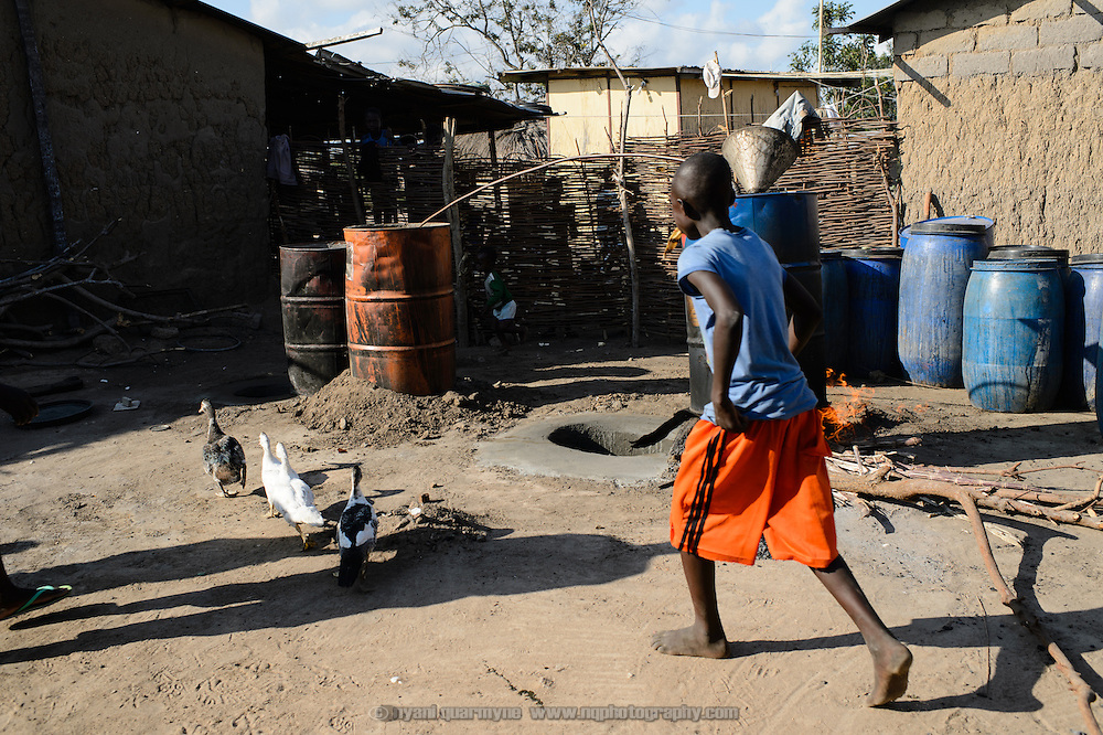 A boy chasing duks away from the vicinity of an akpeteshie still. A strong, clear spirit, akpeteshie is distilled from fermented palm wine or sugar cane juice.