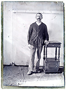 1900s portrait of a furniture maker standing next to a nightstand with little closet and drawer