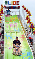 """Callen Murray, 1.5 of Doylestown, Pennsylvania slides down the """"Slide"""" with his grandfather Bob Loughery of Holland, Pennsylvania at Southampton Days Carnival as part of their July 4th celebration Saturday July 4, 2015 in Upper Southampton, Pennsylvania. (Photo by William Thomas Cain)"""
