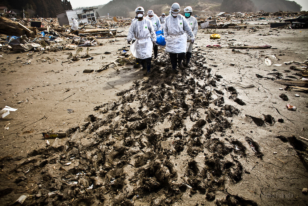 Rescue workers remove bodies from a washed out motorway in Rikuzentakata, Iwate prefecture, Japan more than a week after the area was hit by a 9.0 earthquake and tsunami, Sunday, March 20, 2011. With over 1700 people missing and over 400 dead, Rikuzentakata, having the greatest human loss in the prefecture with nearly 10% of it's population, has an active body search and recovery mission.