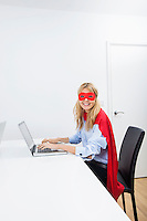Portrait of happy businesswoman in superhero costume using laptop at office