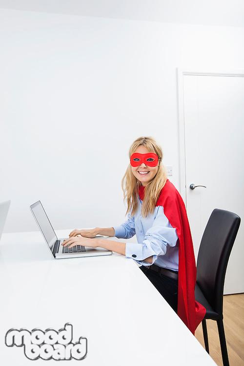 Portrait of happy businesswoman in superhero costume using laptop at office