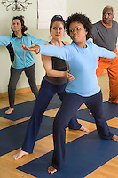 Yoga Instructor Assisting Woman in Yoga Class