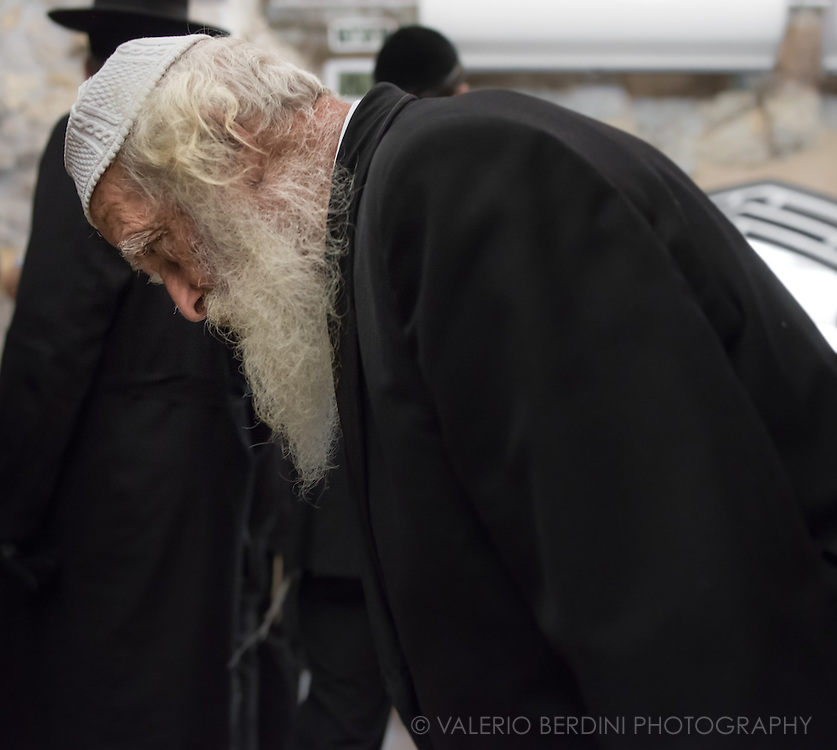 An elder man bows as a sign of respect and devotion as he prays at the Western Wall. He wears a kippah (also known as a yarmulke) a hemispherical cap worn by Jews to fulfill the customary requirement held by some orthodox authorities that the head be covered at all times. It is worn by men at times of prayer. The Western Wall supplies a kippah for temporary use to all male visitors.