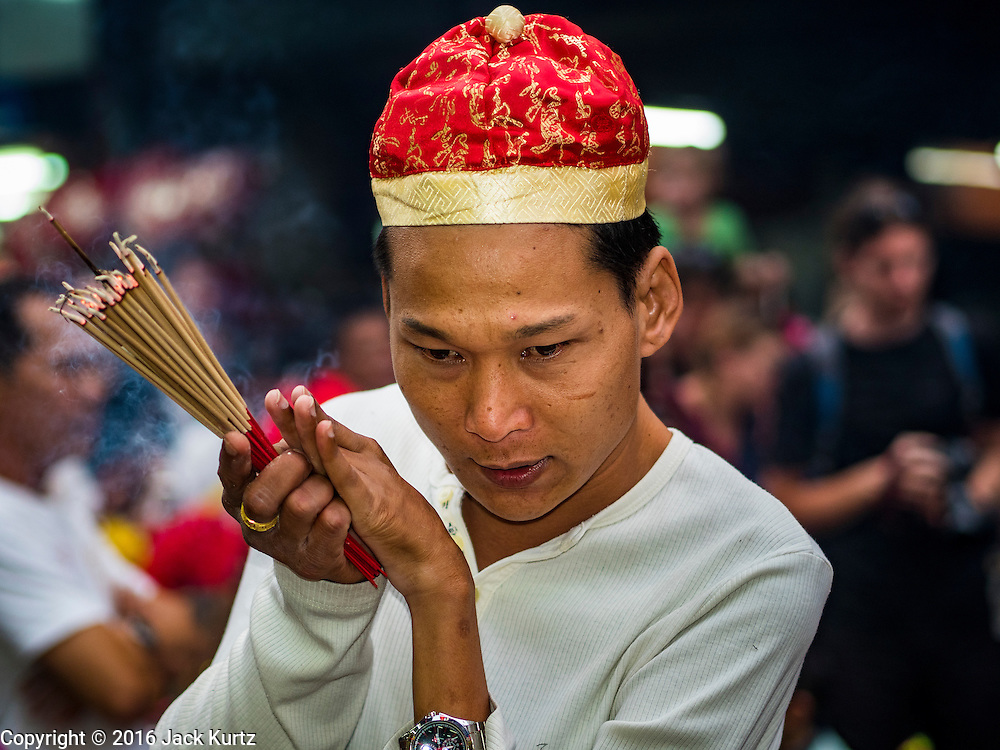 "08 FEBRUARY 2016 - BANGKOK, THAILAND: A man prays in front of a small Chinese shrine in Bangkok's Chinatown district during the celebration of the Lunar New Year. Chinese New Year is also called Lunar New Year or Tet (in Vietnamese communities). This year is the ""Year of the Monkey."" Thailand has the largest overseas Chinese population in the world; about 14 percent of Thais are of Chinese ancestry and some Chinese holidays, especially Chinese New Year, are widely celebrated in Thailand.       PHOTO BY JACK KURTZ"
