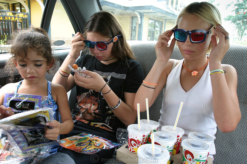 (MODEL RELEASED IMAGE). On the way back from Mackas (Aussie slang for McDonald's), 15-year-old Kayla Samuals (in 50 Cent T-shirt) rips open the Spy Kids 3-D comic book that the restaurant awards to purchasers of Happy Meals. Like her half-sister Sinead Smith (drinking) and her friend Amelia Wilson, Kayla is from an Aboriginal family whose roots lie in the arid outback. But the girls have little interest in outback cuisine; at least for now, Mackas is their culinary mecca. They are visiting a MacDonald's near their home in Riverview, (near Brisbane) Australia. (Supporting image from the project Hungry Planet: What the World Eats.) The Brown family is one of the thirty families featured, with a weeks' worth of food, in the book Hungry Planet: What the World Eats.