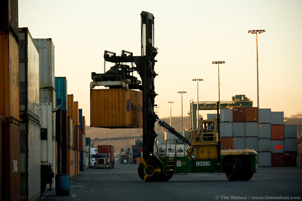 An SSA Marine heavy lift, called a top pick, moves between the busy stacks of containers as it works to stack  incoming cargo containers at Terminal 18 at the Port of Seattle. The diesel fueled heavy machine will soon be running biodiesel, a more environmentally friendly alternative fuel produced from oilseed crops.