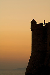 Europe, Croatia, Dalmatia, Dubrovnik.  Female tourist near bastion in old city walls (built 10th century) above Adriatic Sea at sunset.  The historic center of Dubrovnik is a UNESCO World Heritage site.  MR