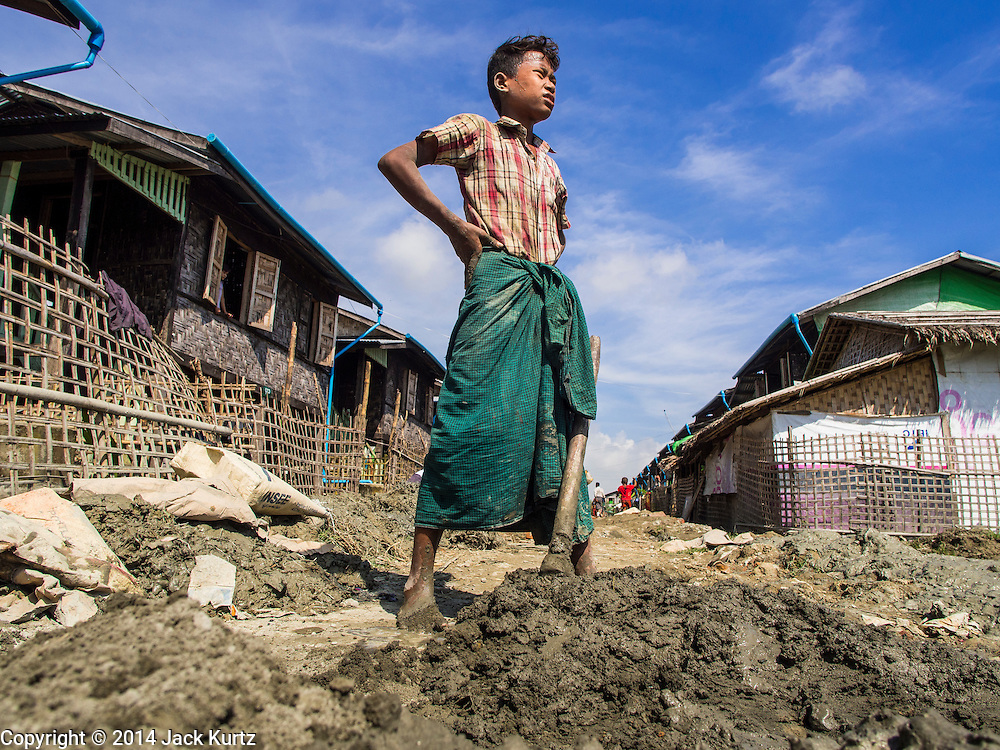 11 NOVEMBER 2014 - SITTWE, MYANMAR: A Buddhist boy takes a break while patching the street in a Rakhine Buddhist IDP camp near Sittwe. About 700 Rakhine Buddhist families live in an Internal Displaced Persons (IDP) camp on the edge of Sittwe. The people in the camp lost their homes in Sittwe in 2012 when Buddhist mobs rioted and burnt down Rohingya Muslim homes and businesses. The Buddhists' homes were mistakenly destroyed by other Buddhists or intentionally destroyed by retaliating Muslims during the 2012 violence. Unlike the Muslims, who live in much larger camps further from Sittwe, the Buddhists are allowed to come and go into downtown Sittwe and their homes are built in the traditional style, on stilts with large windows, and so are much more comfortable.   PHOTO BY JACK KURTZ