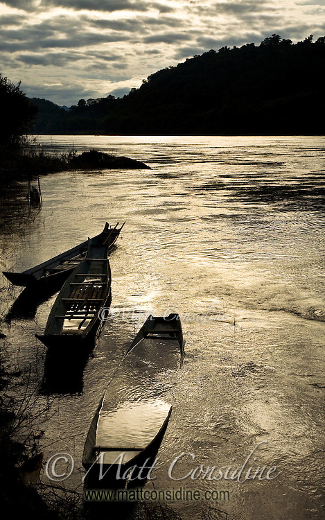 Wooden fishing boats and the golden Mekong river at sunset.