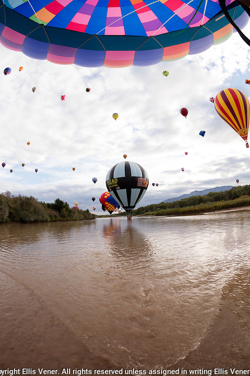 Hot air balloons touching the Rio Grande river near Albuquerque, New Mexico during the annual Albuquerque Balloon Fiesta
