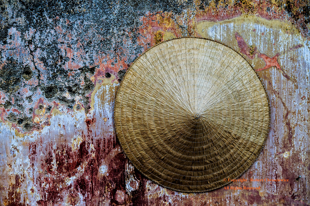A solitary straw hat is left to hang on a very weathered and colourful wall in Hoi An Vietnam.                                                                                                   Headline: A hat left out hanging, Hoi An Vietnam.