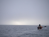 A kayak paddler on the misty ocean outside Spitzbergen
