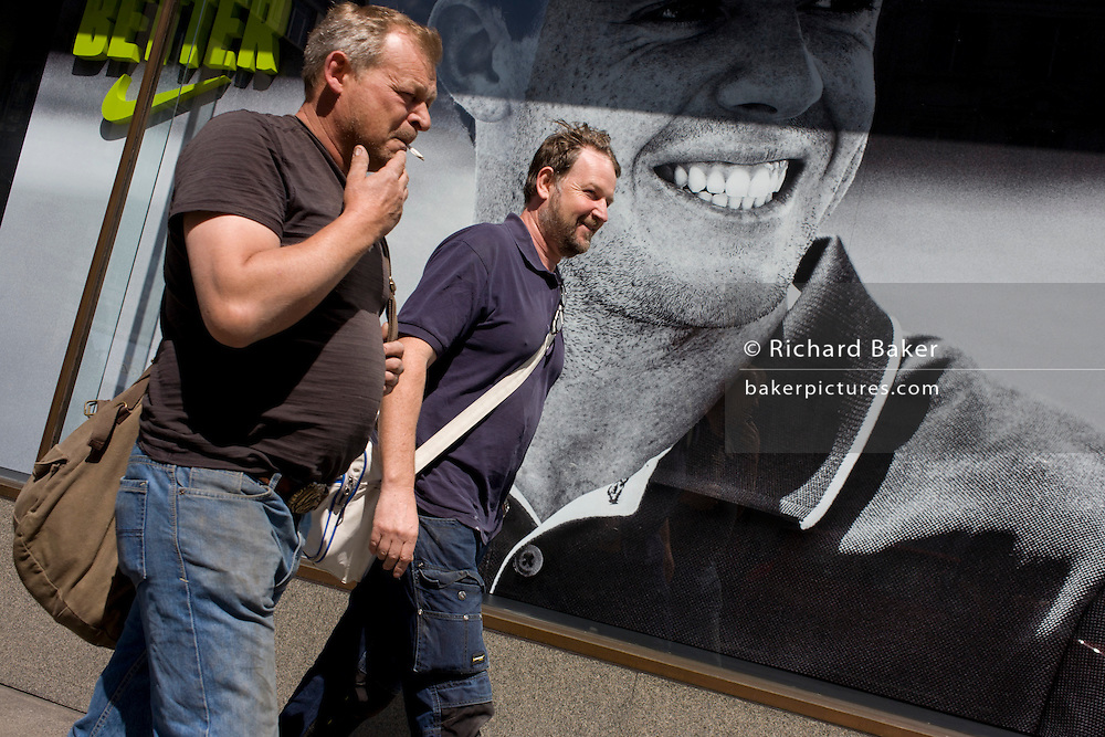 Men pass a Nike retail poster of Northern Irish golfer Rory McIlroy, in central London.