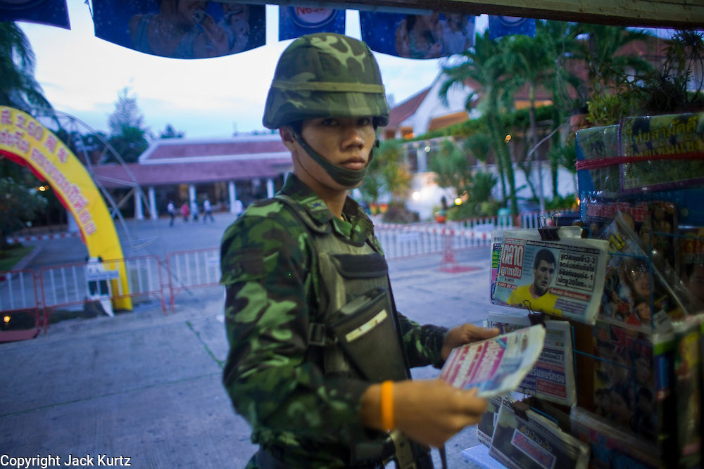 """Sept. 25, 2009 -- PATTANI, THAILAND: A Thai soldier on patrol for Muslim insurgents buys a newspaper in a Chinese owned small shop in Pattani, Thailand. Thailand's three southern most provinces; Yala, Pattani and Narathiwat are often called """"restive"""" and a decades long Muslim insurgency has gained traction recently. Nearly 4,000 people have been killed since 2004. The three southern provinces are under emergency control and there are more than 60,000 Thai military, police and paramilitary militia forces trying to keep the peace battling insurgents who favor car bombs and assassination.   Photo by Jack Kurtz"""