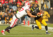 November 02 2013: Iowa Hawkeyes running back Damon Bullock (5) is hit by Wisconsin Badgers linebacker Brendan Kelly (97) on a run during the second half of the NCAA football game between the Wisconsin Badgers and the Iowa Hawkeyes at Kinnick Stadium in Iowa City, Iowa on November 2, 2013. Wisconsin defeated Iowa 28-9.
