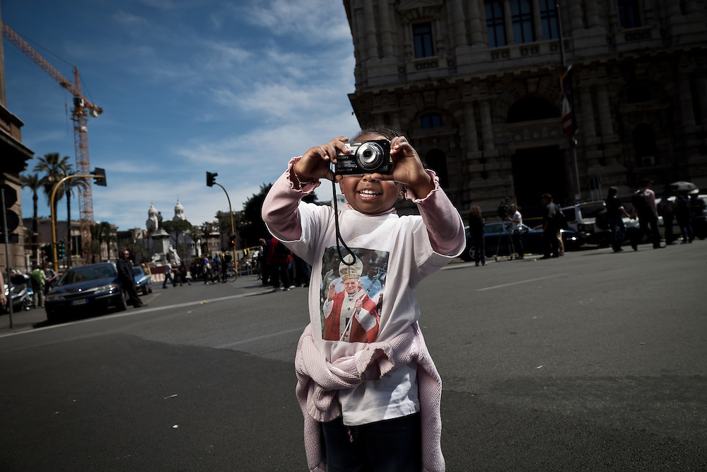 A child wearing the t-shirt of Pope John Paul II takes a picture on the streets of Rome. On 1 May 2011, six years and one month after his death, Pope John Paul II was beatified by his successor Benedict XVI..It is estimated that over one half million people have taken part in the ceremony which was held in St. Peter's Square, the largest crowd in Rome since his funeral. .This is considered the fastest beatification in Church history, the Vatican will have to attribute another miracle to John Paul's intercession after the beatification, only in this case he will be declared a saint.