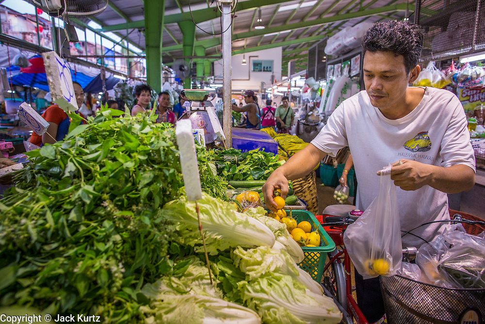 "03 OCTOBER 2012 - BANGKOK, THAILAND:      A man shops for vegetables in Khlong Toey Market in Bangkok. Khlong Toey (also called Khlong Toei) Market is one of the largest ""wet markets"" in Thailand. Thousands of people shop in the sprawling market for fresh fruits and vegetables as well meat, fish and poultry every day.      PHOTO BY JACK KURTZ"