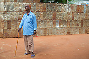 "Dadaab, Kenya -   2014-08-16 - Farah Hayd Ali, survived a shooting at his farm in Somalia that has left him with a bullet lodged in his head but was left partially paralyzed. He is pictured walking near his home in the Hagadera camp in Dadaab, Kenya on August 16, 2014. Farah is now the chairman of a local group of disabled persons in Hagadera Camp. His son, Abdi Farah, 30, witnessed his father being shot in the head and after years of untreated psychological trauma he is mentally unstable and is kept chained in his hut. ""With my disability I can not care for my firstborn son,"" Farah says.  - Photo by Daniel Hayduk"