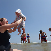 A mother introduces her six month old baby girl, wearing sun protective clothing, to the sea as Cisco Beach, Nantucket, Nantucket Island, Massachusetts, USA. Photo Tim Clayton