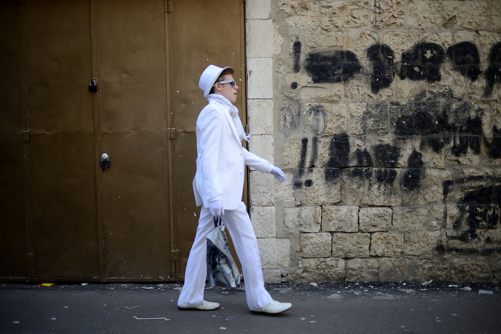 A man waering costume walks during Purim Holiday in the Ultra-Orthodox Jewish neighbourhood of Mea Shearim in Jerusalem, on March 6, 2015. The Jewish holiday of Purim commemorates the salvation of the Jews living with in the borders of the ancient Persian Empire. Purim customs include food gifts, charity, wearing costumes and drinking heavily.