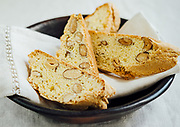 Tratta Dal Forno Italian Biscotti on linen napkin on rustic black bowl which is sitting on a linen table cloth.