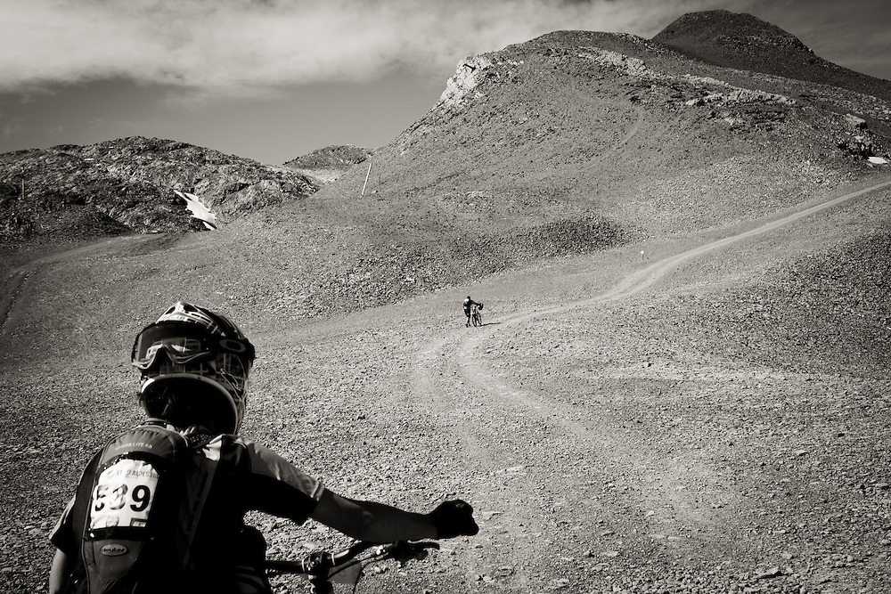 Riders push their bikes through a lunar landscape of shale and rock up towards the start line during the heats.