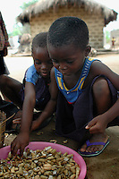 Ghana, Adaklu, Titikope, 2007. Children enjoy going through the groundnuts for sale before they go off to school.