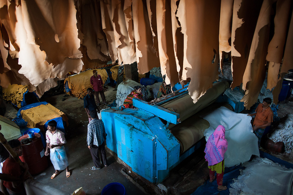 Workers in a Dhaka tannery operate large presses and hang the leather to dry.