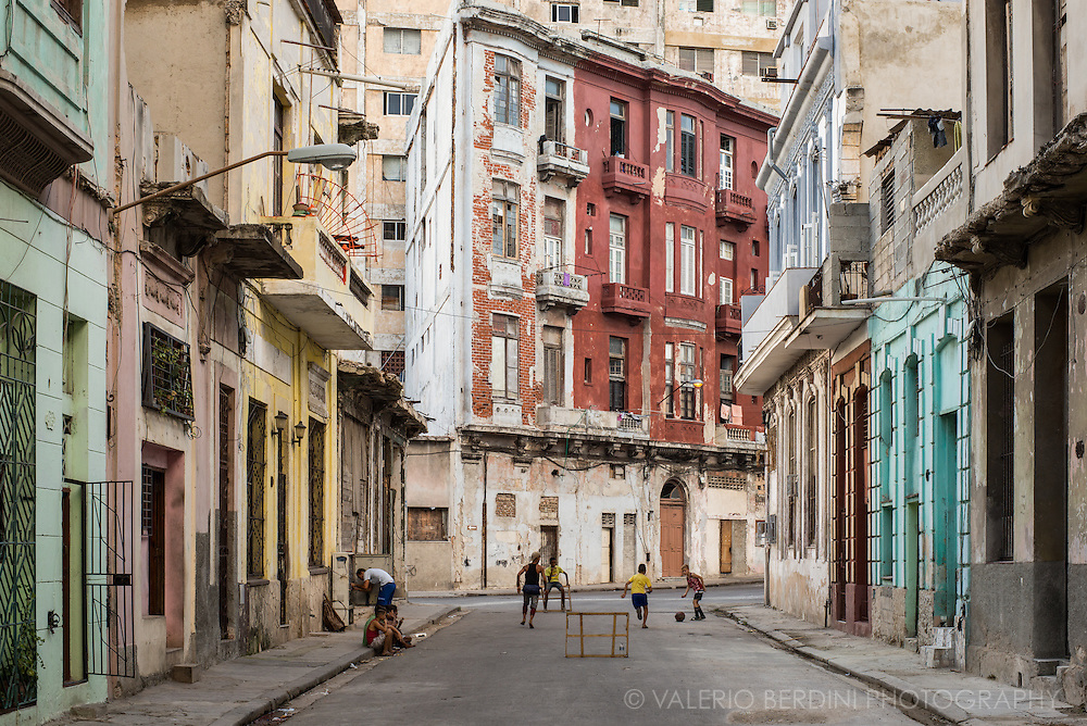 Children play a football match with improvised goal posts in a street of Havana. Cuba, 2015.