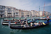 Tourist group sightseeing in gondolas on Canale Grande.