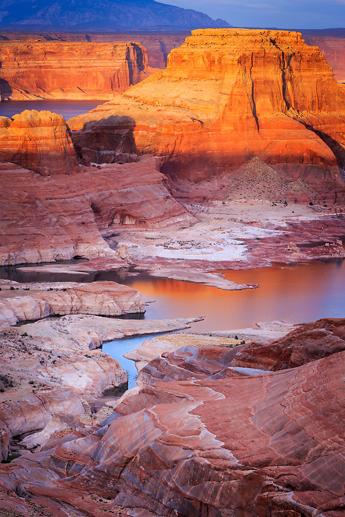 The sun breaks through the clouds at sunset at an overlook for Lake Powell near Page, Arizona.