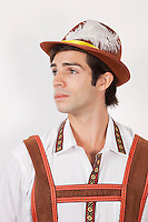 Young man in costume looking away against gray background