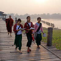 Young students and a monk cross the longest teak wood bridge, the U Bein Bridge, at sunrise in Amarpura, Myanmar (Burma).