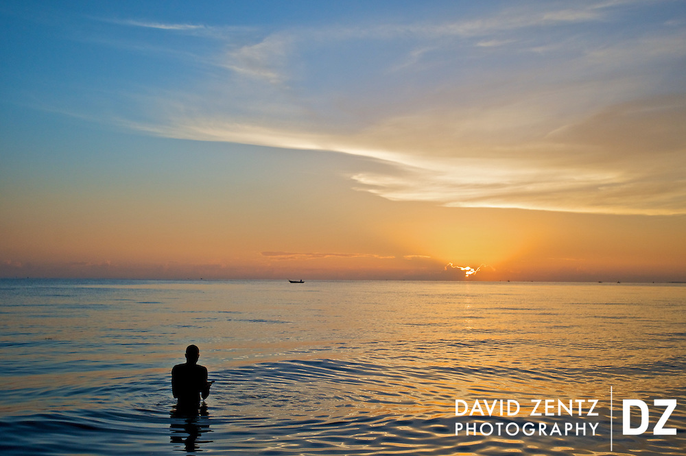 A pilgrim cleanses himself in the sea during a sunrise voodou ritual at Bord de Mer de Limonade, on the north coast of Haiti on July 25, 2008. After renewing their faith in the mud pit at Plaine du Nord on the days prior, pilgrims migrate to the nearby water, their faith renewed.