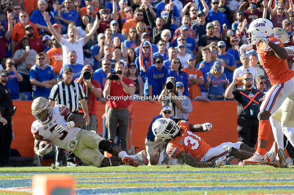 Florida State running back Cam Akers (3) rushes for a touchdown in front of Florida defensive back Shawn Davis (31) during the second half of an NCAA college football game Saturday, Nov. 25, 2017, in Gainesville, Fla. FSU won 38-22. (Photo by Phelan M. Ebenhack)