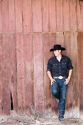 All American cowboy leaning on a rustic barn