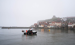© Licensed to London News Pictures. 03/04/2014<br /> <br /> Whitby, North Yorkshire, United Kingdom<br /> <br /> A fishing boat returns to port to unload their catch in Whitby, North Yorkshire as fog shrouds the coastline.<br /> <br /> Photo credit : Ian Forsyth/LNP