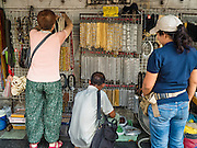 27 NOVEMBER 2015 - BANGKOK, THAILAND:  Shoppers look at amulet cases and chains in a street stall on Maharat Road in Bangkok. Hundreds of vendors sell amulet and Buddhist religious paraphernalia to people in the Amulet Market, a popular tourist attraction along Maharat Road north of the Grand Palace near Wat Maharat in Bangkok. Bangkok municipal officials announced that they are closing the market and forcing vendors to relocate to an area about one hour outside of Bangkok. The closing of the amulet market is the latest in a series of municipal efforts to close and evict street vendors and markets from areas that have potential for redevelopment. The street vendors will be evicted from the area by Sunday, Nov. 29.   PHOTO BY JACK KURTZ