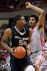 16 November 2014:  Elston Jones picks up his dribble and looks for a shot over Reggie Lynch during an NCAA non-conference game between the Utah State Aggies and the Illinois State Redbirds.  The Aggies win the competition 60-55 at Redbird Arena in Normal Illinois.