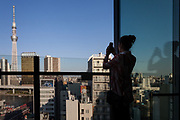 A female tourist takes a photo of Tokyo Skytree from the roof of the Asakusa Tourist Information building. Tokyo, Japan. Monday April 15th 2019