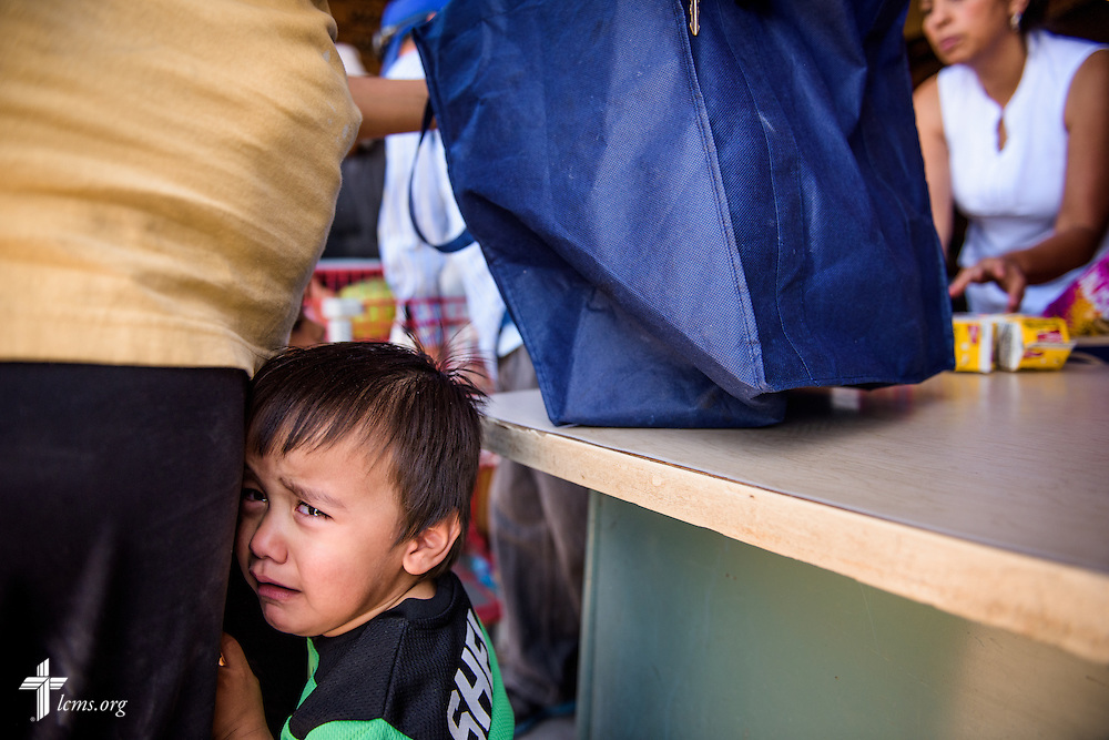A young child cries as his mother receives a food distribution from YLM staff and volunteers on Saturday, May 21, 2016, at  Ysleta Lutheran Mission Human Care in El Paso, Texas. LCMS Communications/Erik M. Lunsford