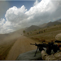 Spc. Brian Stinson, 2nd battalion of the 504th Parachute Infrantry Regiment, keeps a lookout as the convoy heads to shembawat, Afghanistan for a meeting with Lt. Col George Donovan and Gov. Mirjudin Pathan about recent attacks on the school and clinic the army  is costructing in shembawat. Donovan sent a stern message to the towns people that no construction of the clinic or school will continue until they find who is responsible for recent attacks on the buildings.